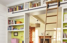 Bookcases arranged to form a passageway unite with flat trim to create a mini library, complete with a rolling ladder to reach great reads on the topmost shelves.