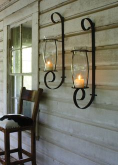 Flat Iron Wall Sconce with Glass Hurricane Rustic Brown Finish. One Hurricane. Sold individually. Price is for one. This rustic, elegant wall sconce features a single strip of metal curling top to bot