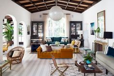 Living room with wooden ceilings, a globe pendant light, and a yellow sofa