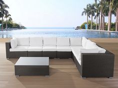 GRANDE patio conversation set made out of brown wicker with white, soft cushions. Perfect for a family gathering.