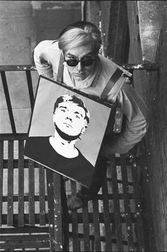 """Andy Warhol with """"Self Portrait"""" mounted on homemade sandwich board on fire escape at the Factory, 1964, by William John Kennedy"""