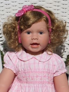 """Lee Middleton """"Little Miss"""" 27"""" toddler designed by Reva Schick is such a precious baby girl with full length vinyl limbs. She has blonde curls and big blue eyes. This little girl is precious. She will come to you as pictured wearing her Tommy Hilfiger dress, diaper cover, white ruffled socks and leather shoes. 