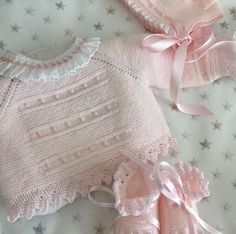 Pale pink baby sweater. Top-down raglan sleeve; garter stitch, bobbles, lace edging. Pretty and easy. ~~ Embellishment: smocked ruffle sewn to the neck