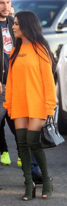 Who made  Kourtney Kardashian's orange shirt dress, black handbag, and gray thigh high boots? | Street Fashion