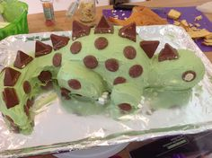 Stegasaurus cake - 11/2 round cakes stood up, tail cut from other half, head and legs cut from square cake, squished together with strawberry jam and slightly carved to shape, covered with dyed buttercream, toblerone for spikes, chocolate buttons for spots and tictacs for claws.