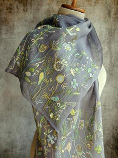 Linen voile shawl embellished with 14 inch hems of embroidery and applique. Background is a grey blue.
