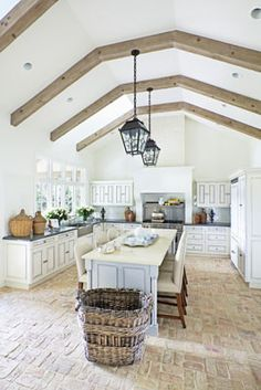 stunning chalky brick floor in a white kitchen - fabulous basket and lanterns!