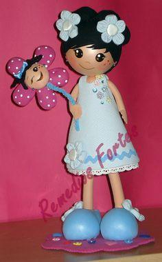 Muñeca fofucha con moñitos y flor.