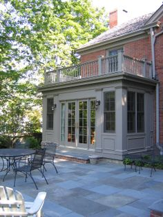 COOK ARCHITECTURAL Design Studio│The sunroom includes French doors that open up to outdoor living space. The stone paving compliments the brick wall and wood trim addition on this North Shore home.
