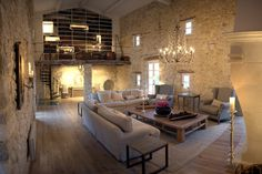 Great hall. Beamed vault. Stone walls. Chandelier. Towering fireplace. Mezzanine. Pale linen apholstery. Wood floors. Les Cavaliers, Provence, France