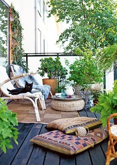 Boho terrace, with soft ethnic patterns, rattan, bamboo, potted plants, a dark floor and a fine cat. By Danielle de Lange