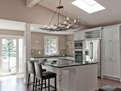 Toronto-based designer Frankie Castro created a natural look in this contemporary kitchen with earth-toned tiles and a tree branch chandelier. Photography by Celebration Studios