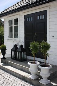 These oversized lanterns look great in front of this bijou cottage - play with scale. White Exterior Houses, Grey Houses, Breakfast At Tiffany's, Black Doors, White Cottage, Outdoor Living, Outdoor Decor, Front Door Decor, Modernism