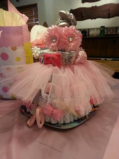 Diaper cake - I made this one myself for my sisters shower. Its 4 tier and no pins!! Fold the diapers in half (front to back) and fan till you have desired size. Tie with ribbon or twine. And stuff middle with more diapers(you can roll and tighten with rubberband or fold them) or fill with goodies :) the only pins I used were to pin the washcloth bows around on each tier. Tutu skirt and two flower clips at top were purchased at hobby lobby in a kit for $9.99