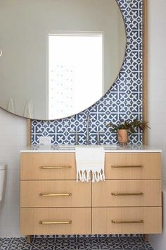 Large, round mirrors are great for making small bathrooms appear larger, and it certainly brings this one alive. The blue tiles and light woods gives proper fresh, spring vibes to this bathroom design. Oversized Round Mirror, Round Mirrors, Huge Mirror, Vanity Design, Bathroom Wallpaper, Modern Bathroom Design, Tile Design, Designer, Low Ceilings