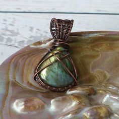 Copper Wire Wrapped Labradorite Cabochon Pendant  This stunning pear shaped Labradorite Cabochon has stunning green/gold flash within it which helped to inspire this unique piece of jewellery. All elements of this piece of jewellery are completely handmade by myself. The pear drop shaped cabochon is wrapped with bare copper wire and embellished with weaves of copper.  I have aged the copper used in this pendant using a patina, a patina speeds up the natural aging process all copper goes ...