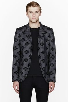 ANN DEMEULEMEESTER //  Grey herringbone velvet jacquard blazer  32378M028001  Long sleeve structured blazer in grey herringbone twill. Black velvet appliques throughout. Notched lapel collar with buttonhole. Button closure at front. Padded shoulders. Breast pockets and welt pockets at front. Vented at back hem. Fully lined. Tonal stitching. Four-button surgeon's cuffs. Shell: 98% fleece wool, 2% spandex. Lining: 65% acetate, 35% rayon. Dry clean. Made in Italy.  $2105 CAD