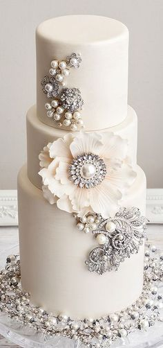 A white cake with pearls, crystals and jewelry is a perfect fit for a glam wedding. Created by De La Creme Creative Studio.