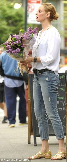 Uma Thurman wore a white peasant blouse tucked into NYDJ skinny jeans and golden sandals while buying flowers at Union Square Greenmarket in NYC