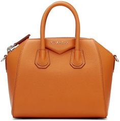 """Structured grained calfskin duffle bag in 'rust' orange. Twin rolled carry handles at top. Detachable and adjustable shoulder strap with lanyard clasp fastening. Logo plaque at face. Zip closure. Zippered pocket, patch pockets, and leather logo patch at interior. Textile lining in beige. Leather bumper studs at base. Silver-tone hardware. Tonal stitching. Approx. 10"""" length x 8"""" height x 5"""" width."""