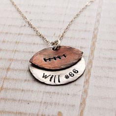 Show your team pride with this hand stamped football necklace. A handcut and custom designed copper football sits on top of a 7/8 stamped sterling silver disc with your players name and number. All pieces are lightly hammered on the edges and oxidized for a rustic and unique piece. Go team Go!!! ♥ ♥ ♥ Please leave your personalization requests in the comments section at checkout.    ♥ ♥ ♥ Chain options are a dainty sterling silver cable chain or an upgraded, thicker diamond cut ball chain. ♥…