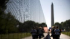 Visitors file by the Wall, which currently contains 58,249 names of fallen soldiers, while visiting the Vietnam Veterans Memorial in Washing...