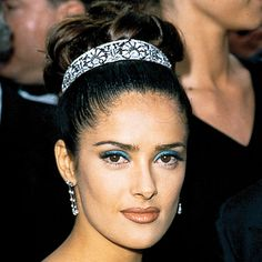 "Salma Hayek Pinault  1997  had the perfect take on a topper. ""I love that the tiara is far back on her head,"" hairstylist Brad Johns said of the updo. ""It's sleek."""