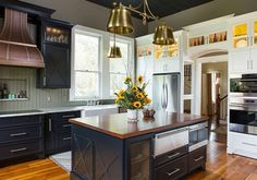 This farmhouse kitchen blends chrome appliances with bronze and copper fixtures, adding edge to a traditional design.