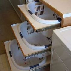These laundry basket pull outs are so clever for sorting laundry! Visit my blog post for more storage solutions.