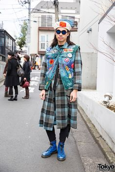 Kinji, the owner of the Harajuku vintage boutique Punk Cake, on the street in Harajuku wearing a plaid coat, a patched denim vest, skinny jeans, and Dr. Martens boots.