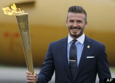 David Beckham holds the Olympic torch during the ceremony to mark the arrival of the Olympic flame to Britain from Greece, at RNAS Culdrose, Cornwall, England, Friday May 18, 2012.