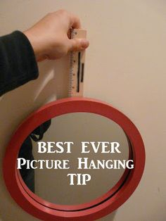 You'll have a little mark on your wall where the nail should go. Hammer one in and voila! You now have the perfect way to hang your picture and no measuring needed!