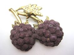A sweet vintage brooch. It is raspberries with a rhinestone studded leaf. The berries appear to be sugared.  Marked Pat Pend. There is some wear