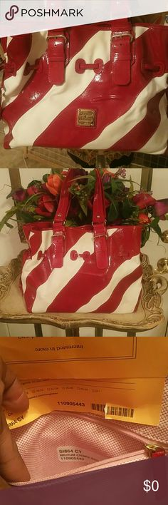 "Dooney & Bourke Chiara Purse This is a medium CHIARA  purse that looks like a candy cane. I know I should have listed it at Christmas but I just got the nerve to let it go. With this purse you can have a little Christmas with you all year round.  It's red patent leather with white canvas contrast. See pic 1 for small 2"" pucker on the front. Also a few light smudges on the white canvas fabric. The inside has two zippered pockets and has original card to register bag. Inside is clean with key…"