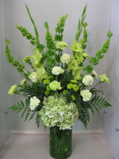 Green wedding or party arrangement. Green Bells of Ireland, Gladiolus, antique hydrangea at Bloomfield Floral. #green #flowers #hydrangea bloomfieldfloral.com Denton,TX