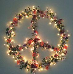 Feminine & lovely peace sign shaped flower wreath wrapped in lights. Love! I'd hang it above my bed as a night light, forever a flower child...