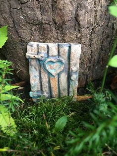 Fairy Door is made from stoneware pottery. Each fairy door is lovingly handmade and has a beautiful, rustic woodland charm with heart window detail. The door has been hand coloured with natural oxide wash. Each door is fired to a high temperature making it frost proof and suitable for outdoor use.  Dimensions: 55mm W x 70mm H x 15mm D  Ideas for use: Attach the door to a skirting board inside your house, a playhouse, tree or secretly hide the door in your garden and wait your new arrivals…