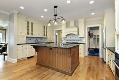 Luxury kitchen with cream color cabinets reclaimed wood island and wood floors