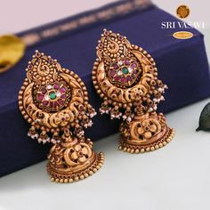 A pair of Yellow gold with an antique finish jhumkas, Earrings Studded with kemp stones hanging gold balls. Gold Jhumka Earrings, Jewelry Design Earrings, Gold Earrings Designs, Antique Earrings, Designer Earrings, Necklace Designs, Jhumka Designs, Gold Jewelry, Jewlery