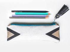 Sturdy little pencil case/cosmetic bag made from genuine off white and black leather with Geometric Leather applications in black and gold.  Ideal to store pens and pencils, cosmetics or art...