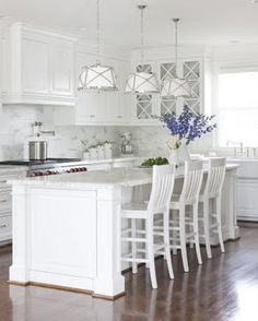 White kitchen with dark floors and white and chrome pendant lights