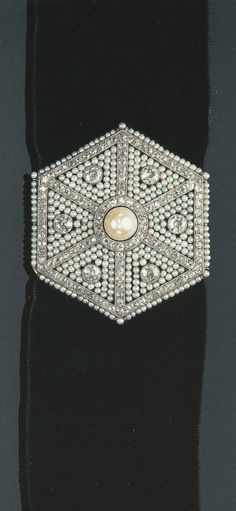 A BELLE EPOQUE PEARL, SEED PEARL, DIAMOND AND VELVET CHOKER, CIRCA 1910. Centring upon a hexagonal-shaped seed pearl panel, set with a button-shaped pearl, accented by old mine and single-cut diamond trim and diamond collets, joined to a detachable wide black velvet band. Source: Christie's, Magnificent Jewels, NY, April 2000.