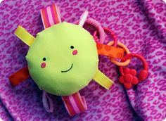 Cute taggie rattle. I love how big she made center and ribbon loops! Great idea for a stroller/carseat toy.