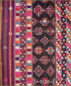 This handsome textile is a traditional woman's wrap around dress known as kira in the Himalayan kingdom of Bhutan. The rectangular form measures 52.5 in. x 92 in and is created of three panels joined in the warp direction and oriented horizontally when worn. The solid black background creates a dramatic foil for the skillfully designed palette of warm orange,red,and maroon contrasted with cool turquoise,green and aqua. Both warm and cool colors are complemented by shades of fuchsia, ecru,and…
