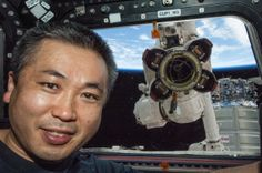 Japan Aerospace Exploration Agency astronaut Koichi Wakata poses for a photo at a window in the Cupola of the International Space Station while the Canadarm2 robotic arm's Latching End Effector appears to be looking through the window from outside the station.