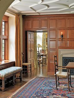 Dining room with paneling, Tudor arch fireplace and quatrefoil firescreen