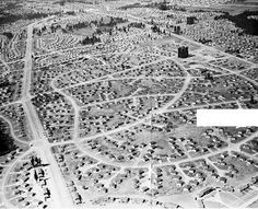 This dramatic view looking west shows McLoughlin Heights in Vancouver, Washington with its 5,500 units of temporary housing. MacArthur Boulevard is at the left, Lieser Road is just under the airplane from which the picture was taken, and Mill Plain Road is at the far right