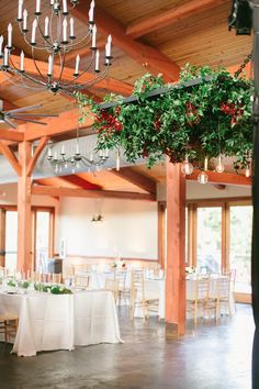 Unique wedding reception idea! Drape greenery from ceiling fixtures for a fresh outdoor look. Great for a summer wedding. #summerwedding #receptiondecorations #weddingflowerssummer