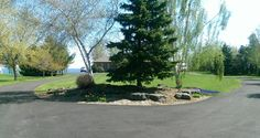 A long circular driveway with a low maintenance center island rock garden welcomes visitors to this lakeside home.