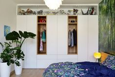 I když této originální ložnici jasně vévodí dřevěná postel Javorina s okrasnou flórou kolem, šatní skříň podél zdi rozhodně také stojí za zmínku. Sestavu tvoří skříně i zásuvky z laminových desek v bílé barvě, uprostřed doplněné o dva výklenky z dubového dřeva. V nich se našlo perfektní místo pro zavěšení oblíbených svršků, zatímco zbytek garderoby je uspořádaný uvnitř. Prosklená vitrína nahoře pak ukrývá úctyhodnou sbírku vesmírných lodí z předaleké galaxie… Entryway, Furniture, Home Decor, Entrance, Decoration Home, Room Decor, Door Entry, Mudroom, Home Furnishings